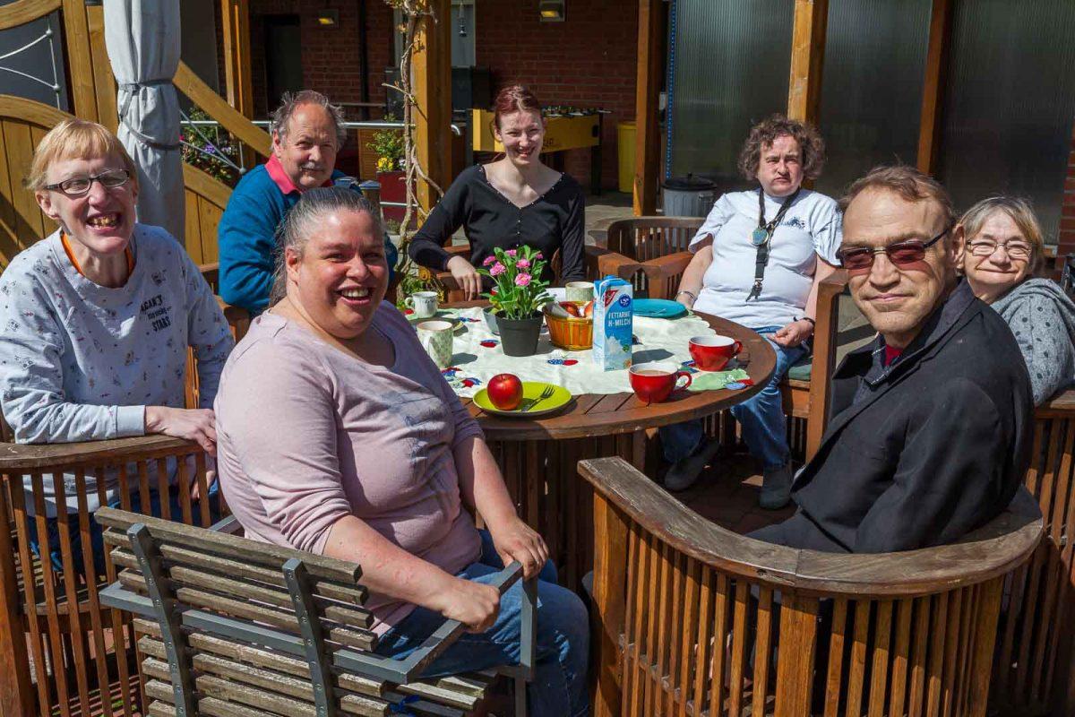 Die Wohngruppe genießt Kaffee und Kuchen im Garten